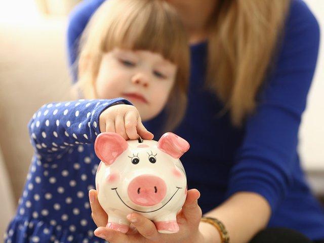 Child Putting Money in Piggy Bank.jpg
